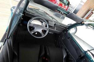 Im Cockpit ein kleines Lenkrad, Schalensitze und die urige Krückstock-Schaltung